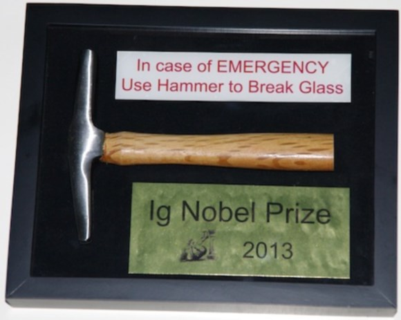 "The 2013 Ig Nobel Prize, designed and built (as per tradition) by Eric Workman. This year's prize is a hammer, sealed inside a transparent glass box, with a sign on the outside that says, ""In case of emergency use hammer to break glass"". Image: Improbable Research"