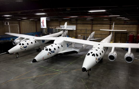 The Scaled Composites SpaceShipTwo spaceplane (central fuselage) resting under its mothership, White Knight Two, inside a hangar in Mojave, Ca., USA. Image: Virgin Galactic/Mark Greenberg via Wikimedia Commons